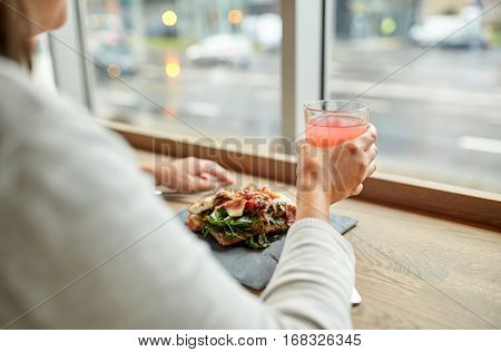 food, drink, eating and people concept - woman with glass of juice and prosciutto ham salad on stone plate at restaurant