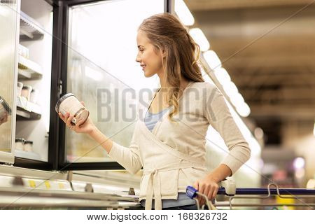 sale, food, shopping, consumerism and people concept - woman with ice cream at grocery store freezer