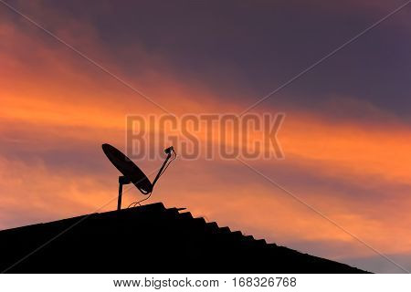 Landscape : color sky in evening with silhouette roof and  satellite dish.