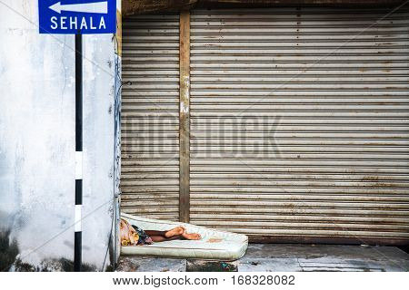 GEORGETOWN PENANG MALAYSIA - JANUARY 26 2017: Poor homeless man sleeps on the streets on a mattress. The legs in the open air lying in the street.