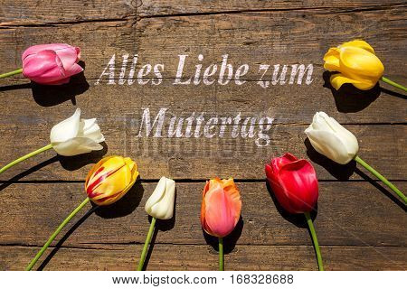 Tulips On Wooden Background And German Text For Mother´s Day