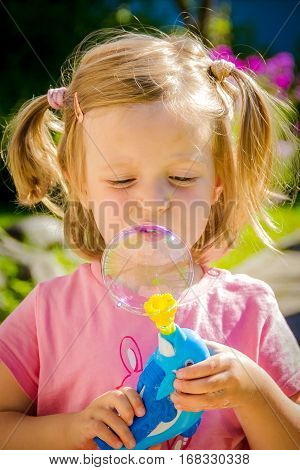 Child play with soap bubbles one sommer day