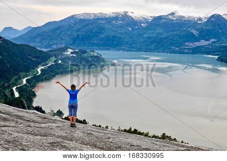 Young woman on cliff over the ocean. Stawamus Chief Peak. Squamish. Whistler. British Columbia. Canada.