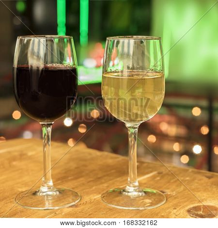 Square photo of red and white wine glasses on a blurred background of lights, selective focus