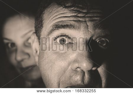 Frightened woman looks out because of a shoulder of a confused man. Black and white portrait,  vintage style.