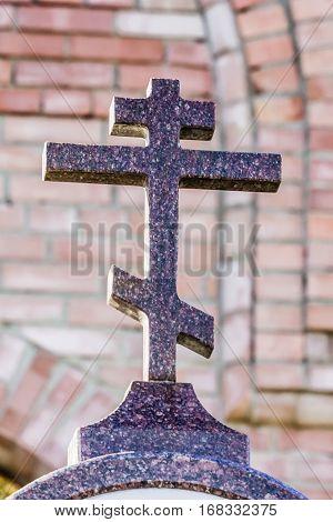 Orthodox cross made of granite. red bricks background