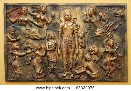 KOLKATA,INDIA - FEBRUARY 09, 2016: Jealous god Sangama tests Mahaviras enderance and, courage by twenty severe tests: Mahavira is victorius, Street bass relief on the wall of Jain Temple in Kolkata