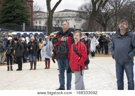 WASHINGTON DC - JANUARY 20: Man with hand to heart during American anthem at Inauguration of Donald Trump. Taken January 20 2017 in District of Columbia.