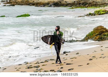 Middleton Australia - August 14 2016: Surfer holding his surfing board at Middleton Beach on a day. Middleton is one of the most famous places for surfing in South Australia