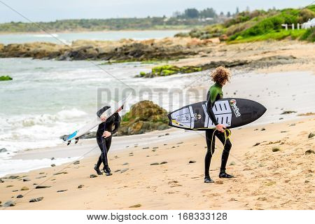 Middleton Australia - August 14 2016: Surfers with surfing boards getting out of water at Middleton Beach on a day. Middleton is one of the most famous places for surfing in South Australia