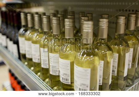 sale and alcohol concept - close up of bottles at liquor store