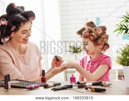 Happy loving family. Mother and daughter are doing hair, manicures, doing your makeup and having fun. Mom and girl sitting at dressing table at house.
