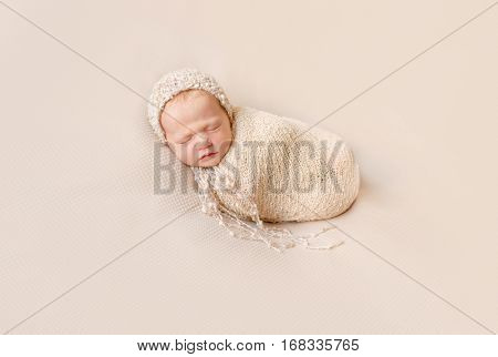 lovely wrapped newborn baby in knitted hat sleeping on a beige blanket