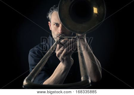 Portrait of a musician with an old dusty trombone on a dark background