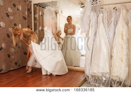 A Bride-To-Be shopping for A Wedding Dress with a girlfriend and having fun in a Bridal Boutique
