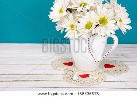 daisy bouquet in white coffee mug with red heart