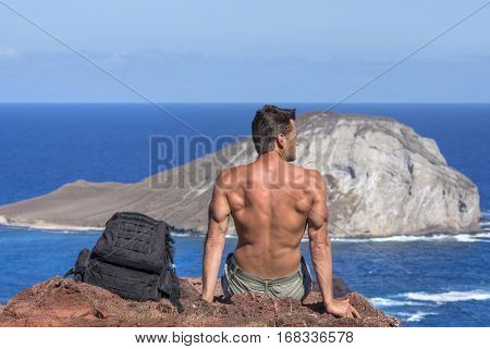 Muscular shirtless Caucasian man sits on rock next to backpack while viewing islands in blue ocean on sunny day in Hawaii