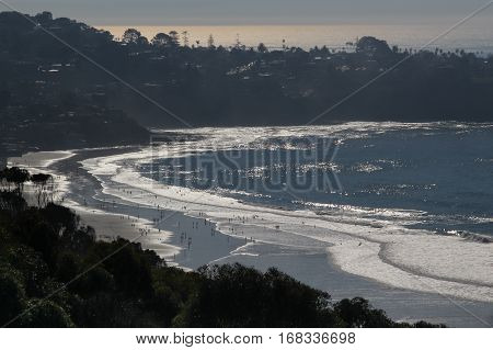 LaJolla Shores Beach, California viewed from hillside, white foamy waves and silhouetted land