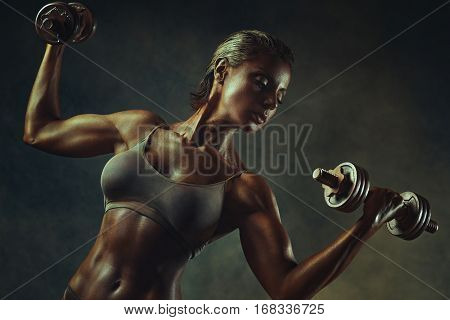 Strong woman bodybuilder standing with dumbbells on wall background. Ancient bronze colors effect.