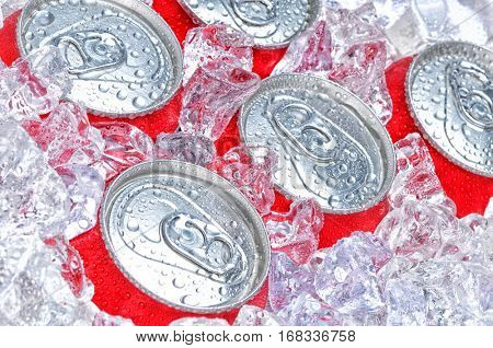 Closeup of a group of soda cans in ice with condensation.