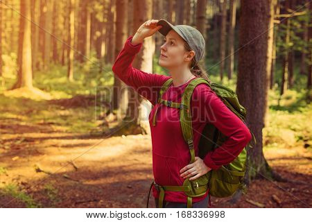 Young woman tourist in red clothing with green backpack looking aside in forest