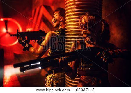 Two women with big guns war fighting thriller concept. Dark red dramatic light and urban interior.