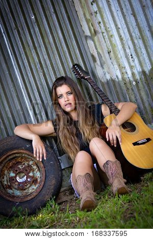 Beautiful rural country guitar girl sitting
