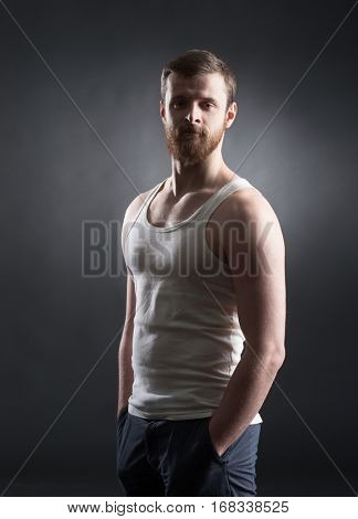 Strong, handsome and bearded man in sleeveless shirt over black background.