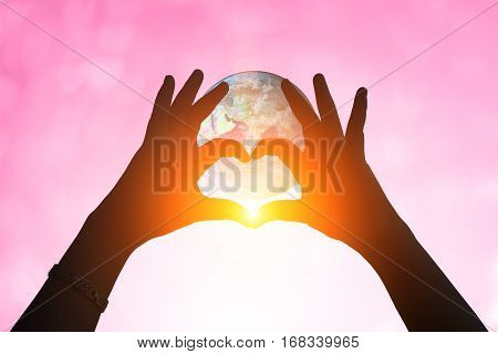 Earth And Hands Under A Heart-shaped Silhouette .blurred Background Of Valentine's Day Concept. Past
