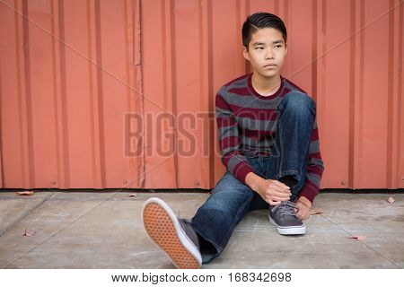 Sad teen Asian boy sitting against a wall looking pensive and off the the left.