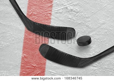 Two hockey sticks and puck on the ice hockey rink. Concept hockey