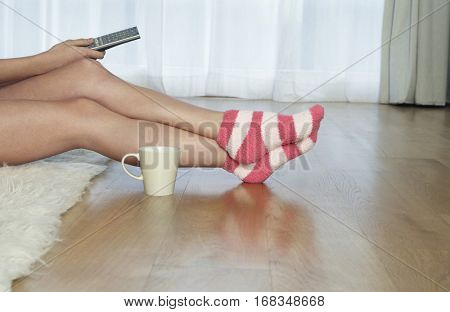 Lowsection of a woman in stripey socks holding remote control