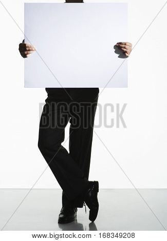 Full length of a silhouette man standing with a large blank card