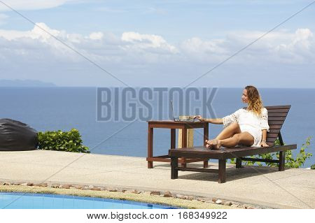 Young woman in white dress doing online shopping outdoors