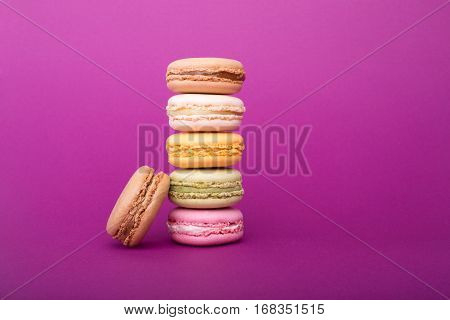 Tower Of Sweet Colorful French Macaroons Or Macarons Biscuits On Purple Background