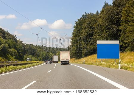 Empty blue sign board at the roadside on freeway in summer landscape. Add your own text. Strategy blank sign on a highway as a clear plan and solutions for business leadership with copy space. Cars trucks and lorries on the road.