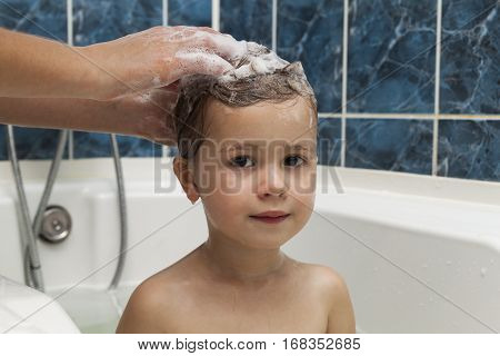 Mom's hands washing little girly's head in the bathroom. The symbol of purity and hygiene education.