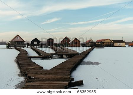 Small weekend houses on frozen lake