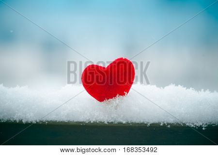 red heart in snow on fence Valentines day symbol closeup