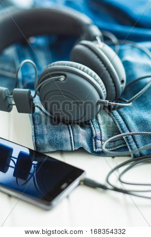 The headphones, cellphone and blue jeans.