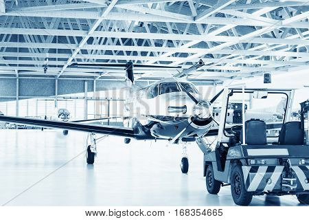 New single turboprop aircraft in big hangar. Focus on nose aircraft colored on technical blue.