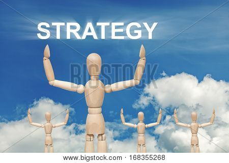 Wooden dummy puppet on sky background with word STRATEGY. Abstract conceptual image