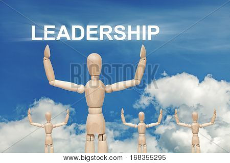 Wooden dummy puppet on sky background with word LEADERSHIP. Abstract conceptual image