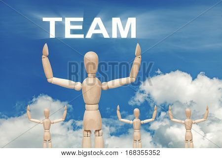 Wooden dummy puppet on sky background with word TEAM. Abstract conceptual image