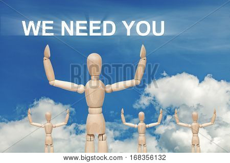 Wooden dummy puppet on sky background with words WE NEED YOU. Abstract conceptual image