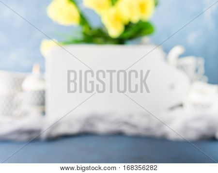 White board mock up tea party set and Easter pastel color yellow flowers on blue. Unfocused background