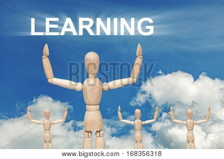 Wooden dummy puppet on sky background with word LEARNING. Abstract conceptual image