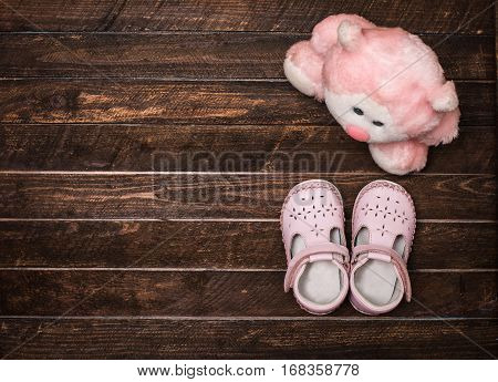Little shoes and a toy on a dark wooden floor. Pair of baby girl shoes. Top view. Toned.