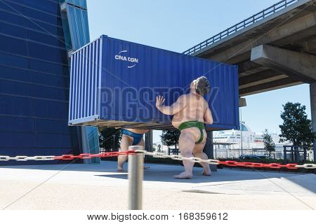 MARSEILLE, FRANCE - AUG 1, 2016: sculpture It Takes Two to Tango by Scottish sculptor David Mach is seen in front of headquarters of CMA-CGM shipping company office tower in port of Marseille