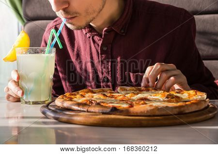Having lunch and soft drink at pizzeria. Hungry male person drinking lemonade and taking slice of pizza at restaurant on bright sunny day
